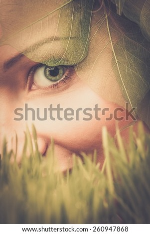 Smiling young woman hiding in a fresh spring grass  - stock photo