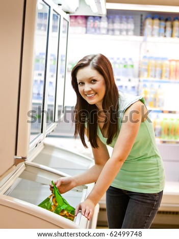 Smiling young woman holding a deep-frozen product in a supermarket - stock photo