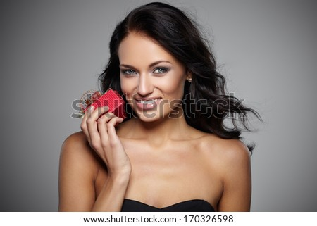 Smiling young woman holding a gift in a red box on grey background - stock photo