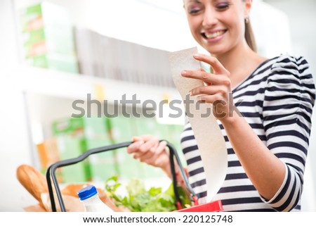 Smiling young woman holding a long grocery receipt at supermarket. - stock photo