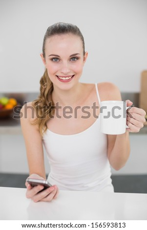 Smiling young woman holding a mug and texting with smartphone in the kitchen at home