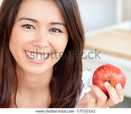Smiling young woman holding a red an apple in kitchen - stock photo