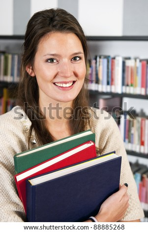 Smiling young woman holding a stack of colorful hardcover books in a library