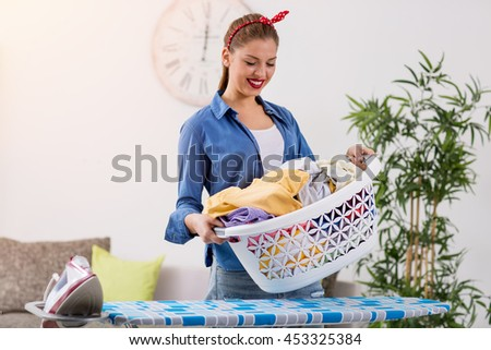 Smiling young woman holding basket with clean clothes - stock photo