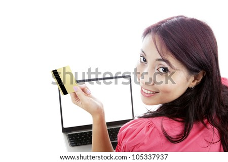 Smiling young woman holding credit card for online shopping with laptop isolated on white