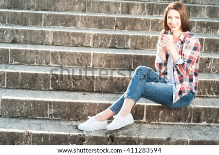 Smiling young  woman holding cup of coffee and wearing casual clothes while standing on stone stairs with copyspace - stock photo