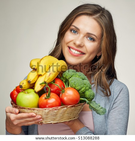 Smiling young woman holding fruit set. isolated portrait.