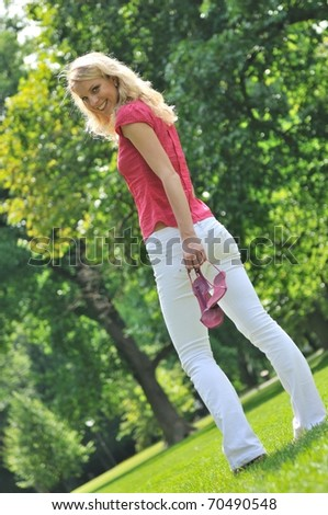 Smiling young woman holding her shoes and walking barefoot on grass in park