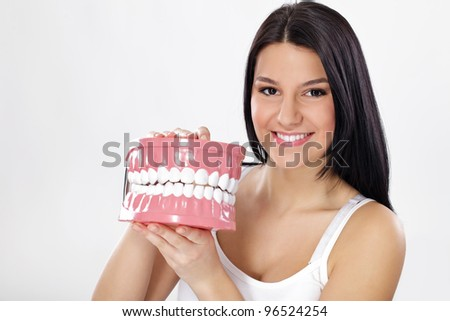 Smiling young woman holding plastic big model of jaws with teeth