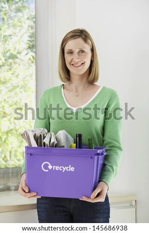 Smiling young woman holding recycling container