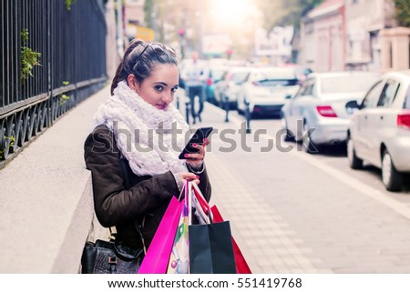 Smiling young woman holding shopping bags and mobile phone while standing outdoors. Shopping woman text messaging. Pretty brunette using her smart phone and holding shopping bag outside