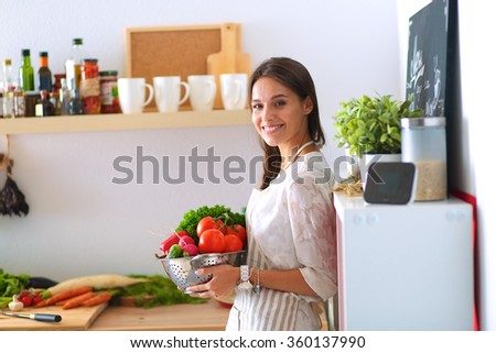Smiling young woman holding vegetables standing in kitchen - stock photo