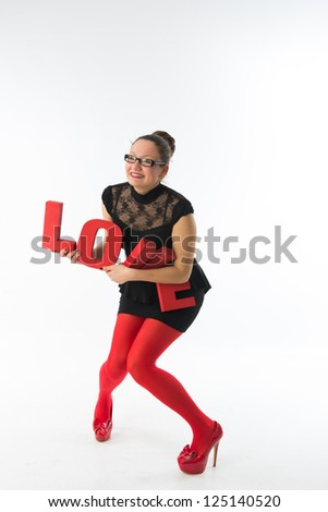 smiling young woman holds a large 3d letters love. - stock photo