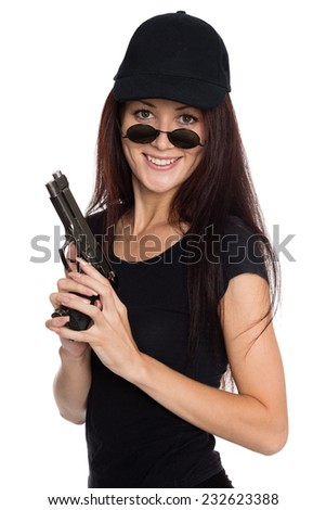 Smiling young woman in a black baseball cap with a gun. - stock photo