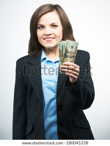 Smiling young woman in a black jacket. Holding dollars. On a gray background