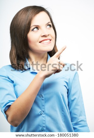 Smiling young woman in a blue blouse. Indicates her finger in the upper left corner. On a gray background - stock photo