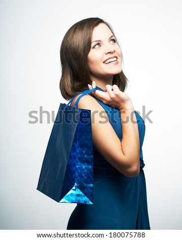 Smiling young woman in a blue dress. Holding gift bag and looking into the upper-left corner. On a gray background