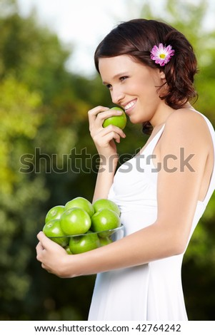 Smiling young woman in a summer garden with apples - stock photo