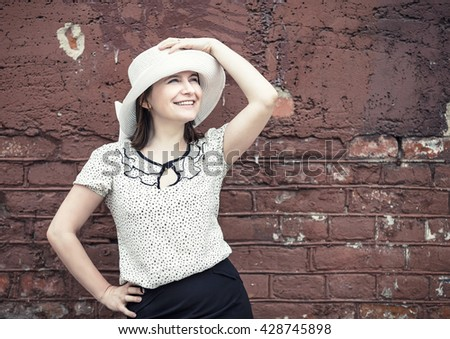 Smiling young woman in a white blouse and a hat posing against vintage brick wall background. Vintage portrait of a woman. Toned photo with copy space. Vintage style photo. - stock photo