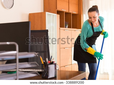 Smiling young woman in apron and gloves cleaning office room