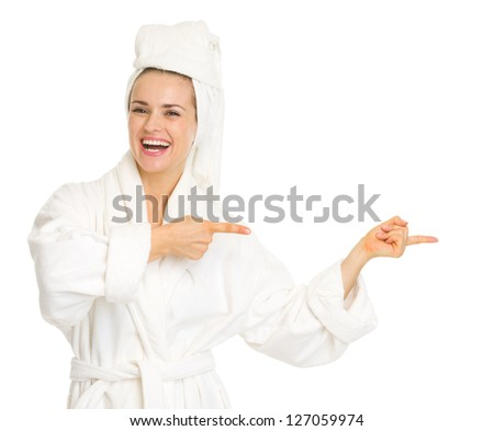 Smiling young woman in bathrobe pointing on copy space