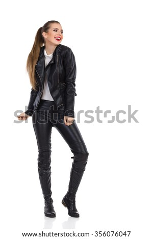 Smiling young woman in black leather trousers, jacket and boots posing and looking away. Full length studio shot isolated on white.