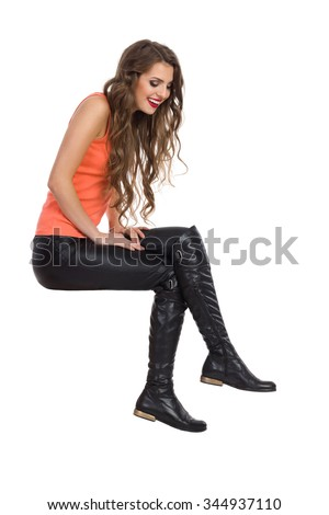 Smiling young woman in black leather trousers, orange shirt and boots sitting on white space and looking down. Side view, Full length studio shot isolated on white. - stock photo