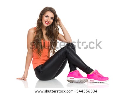 Smiling young woman in black leather trousers, orange shirt and pink sneakers sitting on floor and looking at camera. Side view, Full length studio shot isolated on white. - stock photo