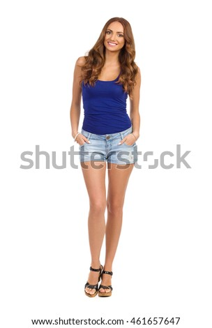 Smiling young woman in blue shirt, jeans shorts and cork heels standing with hands in pocket and looking at camera. Full length studio shot isolated on white.