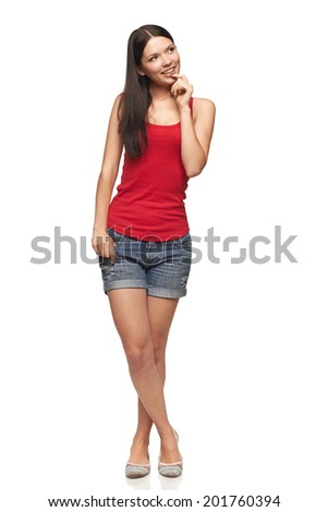 Smiling young woman in bright red top standing relaxed with hand on chin, looking away, over white studio background - stock photo