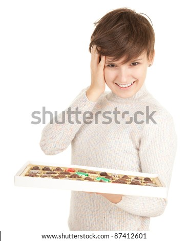smiling young woman in bright sweater with chocolates