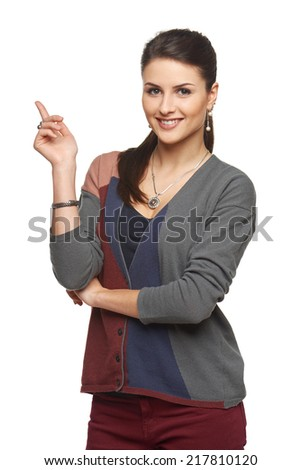 Smiling young woman in cardigan pointing at blank copy space, looking at camera, over white background - stock photo