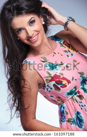 smiling young woman in casual dress playing with her hair