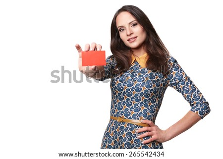 Smiling young woman in colorfull dress showing a card. Isolated - stock photo