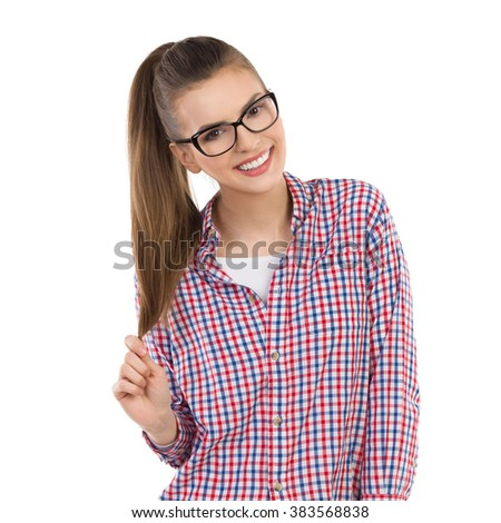 Smiling young woman in glasses and lumberjack shirt posing and holding her ponytail in hand. Waist up studio shot isolated on white. - stock photo