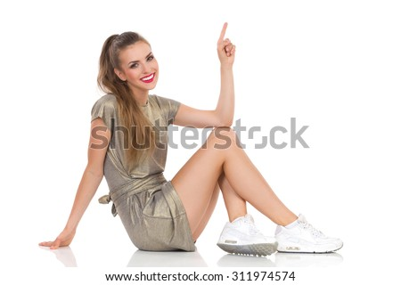 Smiling young woman in gold mini dress and white sneakers sitting on a floor, looking at camera and pointing up. Full length studio shot isolated on white. - stock photo
