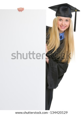 Smiling young woman in graduation gown looking out from blank billboard