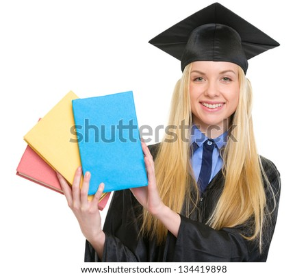 Smiling young woman in graduation gown showing books
