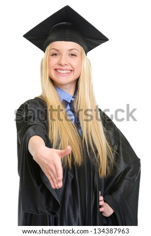 Smiling young woman in graduation gown stretching hand for handshake