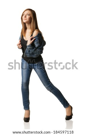smiling young woman in jeans and jacket posing on white background