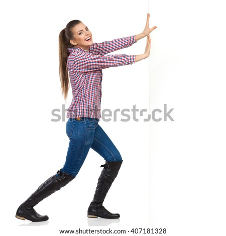 Smiling young woman in jeans, black boots and lumberjack shirt pushing a white wall and looking at camera. Side view, full length studio shot isolated on white.