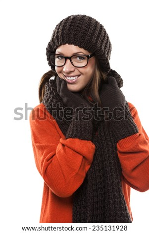 Smiling young woman in modern glasses wearing a winter ensemble of matching, gloves, hat and scarf looking at the camera with a friendly smile, on white - stock photo