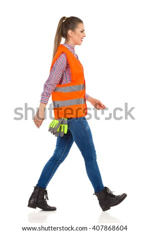 Smiling young woman in orange reflective vest, lumberjack shirt, jeans, black boots,walking and looking away. Side view. Full length studio shot isolated on white.