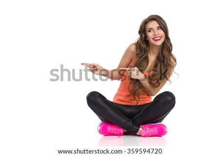 Smiling young woman in orange shirt, black leather trousers and pink sneakers sitting on a floor with legs crossed, pointing and looking away. Full length studio shot isolated on white. - stock photo