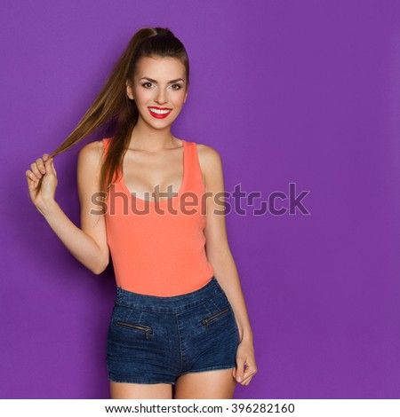 Smiling young woman in orange shirt posing and holding her long hair in hand. Three quarter length studio shot on purple background. - stock photo