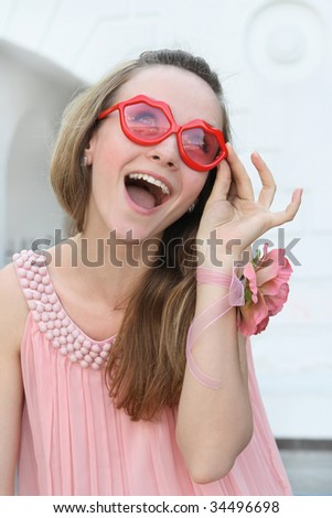 smiling young woman in pink dress and sun glasses