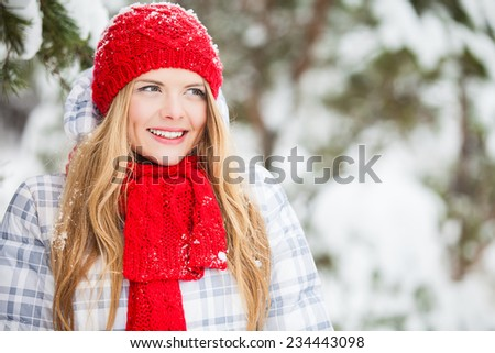 smiling young woman in red hat, scarf and mittens over winter forest