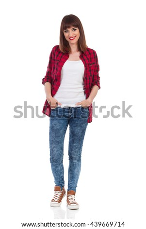 Smiling young woman in red lumberjack shirt, jeans and brown sneakers standing with hands in pocket and looking at camera. Full length studio shot isolated on white. - stock photo