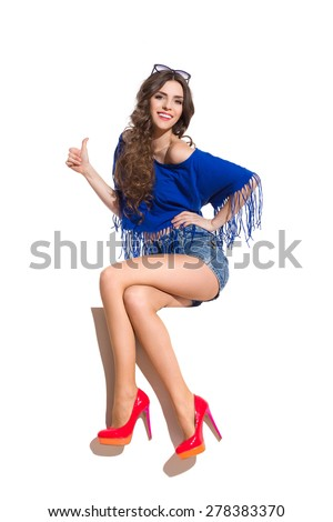 Smiling young woman in sunglasses, blue top, jeans shorts and red high heels sitting at the top of white banner with legs crossed and showing thumb up. Full length studio shot isolated on white. - stock photo