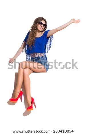 Smiling young woman in sunglasses, blue top, jeans shorts and red high heels sitting at the white banner with legs crossed at knee and waving hand. Full length studio shot isolated on white. - stock photo